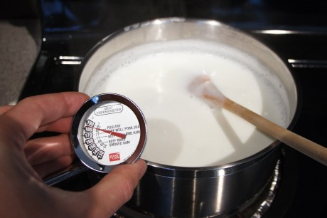 A meat thermometer measuring the temperature of a pot of milk